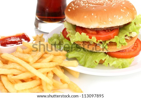 Big and tasty hamburger on plate with cola and fried potatoes close-up