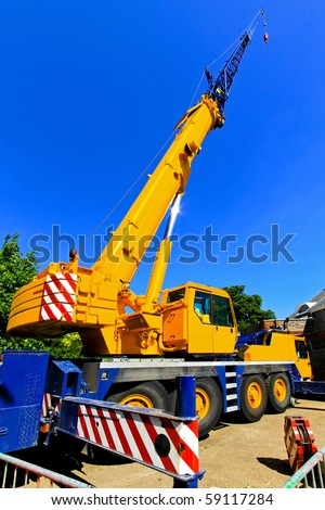 Big and yellow construction crane for heavy lifting - stock photo