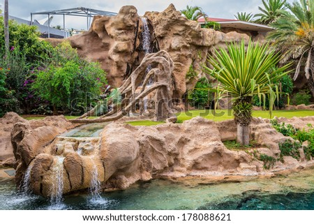 Big animal enclosure in a zoo with a waterfall. - stock photo