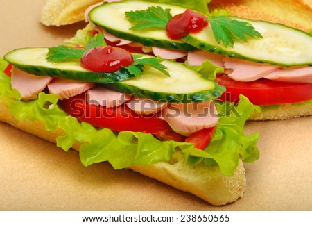 Big appetizing fast food baguette sandwich with lettuce, tomato and frankfurter. Junk food