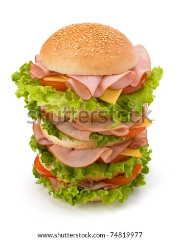 Big appetizing fast food sandwich with lettuce, tomato, smoked ham and cheese isolated on white background.
