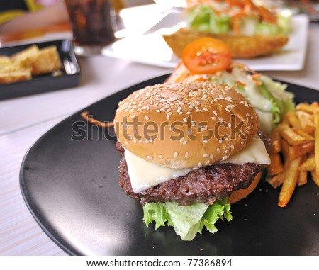 Big appetizing fast food sandwich with lettuce, tomato, smoked ham and cheese . Junk food hamburger. - stock photo