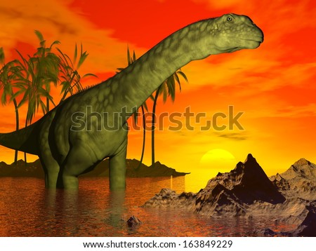 Big argentinosaurus dinosaur standing in water next to palm trees and looking at the beautiful sunset - stock photo
