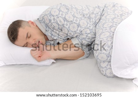 Big baby in pajamas. Side view of infant adult man sleeping on the baby bed - stock photo