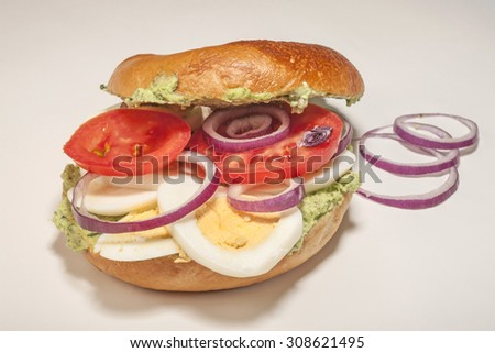 Big bagel sandwich with tomato cheese and ham on white background