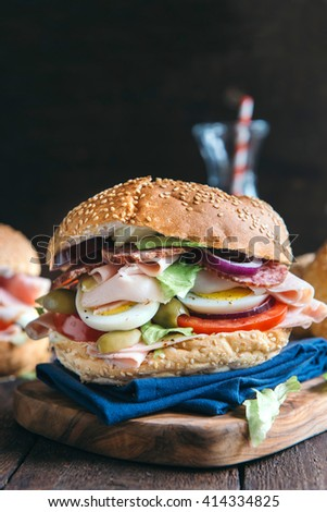 Big bagel sandwich with turkey breast and eggs served on wooden board,selective focus  - stock photo