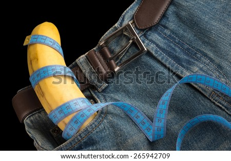 Big Banana like the penis, men's jeans, belt and centimeter, top view, on dark background - stock photo