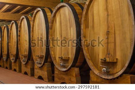 Big barrels with wine in the winery cellar - stock photo