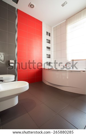 Big bathroom with grey and red tiles - stock photo