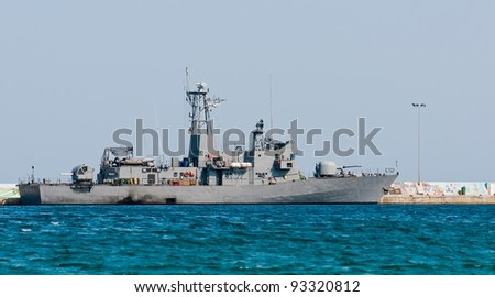 Big battle ship in the dock against blue sky and mountains - stock photo