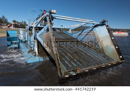 Big Bear Lake, California, June 17, 2016 : An aquatic weed harvester removes weeds from the lake in preparation for the Big Bear Triathlon June 18, 2016 - stock photo