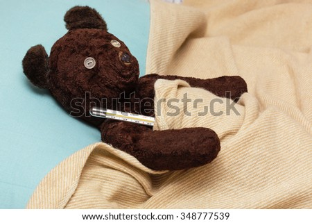 Big bear toy is sick with influenza, measures the temperature in the bed - stock photo