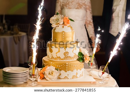 Big beautiful golden wedding cake with flowers next to bride and groom - stock photo