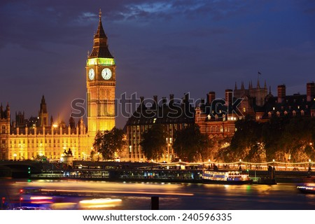 Big Ben and Houses of Parliament with blur ships on thames river at night, London, United Kingdom, UK - stock photo