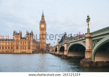 Big Ben and Parliament building at early morning in London with Westminster bridge on the right and Thames river in foreground - stock photo
