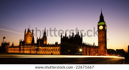 Big Ben and the Houses of Parliament at night. View from Westminster Bridge showing the illuminated buildings against a twilight colored sky. Traffic makes light trails over the bridge - stock photo