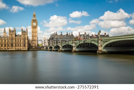 Big Ben and the Houses of Parliament in London with Westminster Bridge and the River Thames in the foreground against a blue sky with fluffy white clouds - stock photo