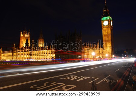 Big Ben and Westminster Abbey at night with traffic rushing passed/ Big Ben and Westminster Abbey at night - stock photo
