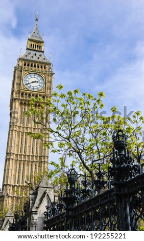 Big Ben behind park's forging fence in sunny spring day. London, UK. - stock photo