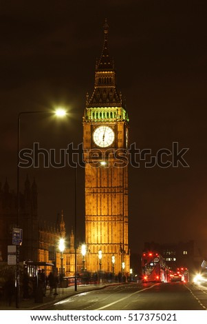 Big Ben closed up at night, red buses present