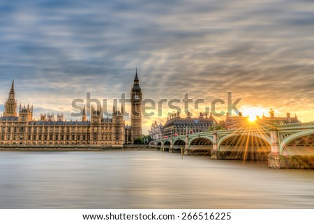 Big Ben, Parliament and Westminster Bridge viewed from South Bank of the River Thames at sunset. The setting sun's rays splash across Westminster Bridge. - stock photo