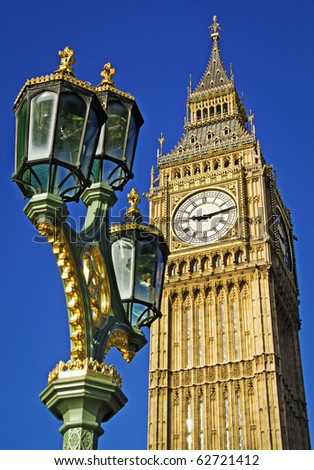 Big Ben seen from Westminster Bridge with an ornate lamp post in the foreground. Clear summer sky. - stock photo
