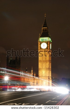 Big Ben with a double-decker bus passing by at midnight;   London, England - stock photo