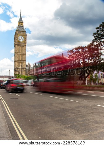 Big Ben with the Houses of Parliament and a red double-decker bus and taxi - stock photo