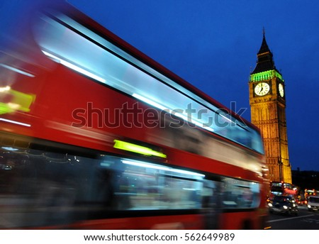 Big Ben with the Houses of Parliament and a red double-decker bus passing at night, London,