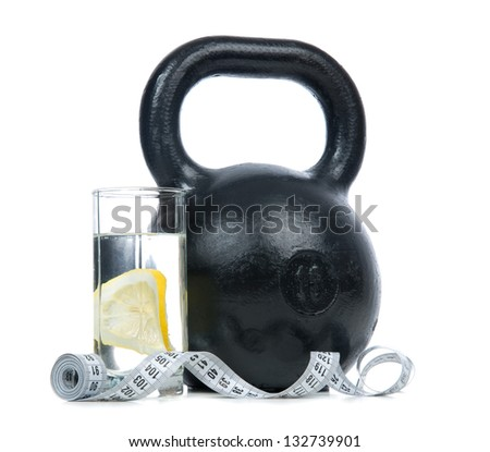 Big black fitness weight with tape measure and glass of drinking water with lemon isolated on a white background. Healthy lifestyle weight loss concept - stock photo