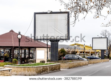 big blank billboard and blank advertisement on the walls of buildings on the background of cafes, restaurants and entertainment attractions on the Black Sea coast, Golden Sands, Bulgaria - stock photo