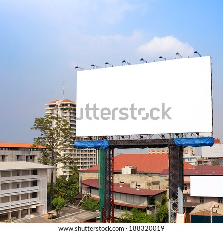 Big blank billboard in Bangkok City, surrounded by highrise buildings and a bright blue sky overhead - stock photo