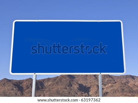 Big blank blue road sign with desert mountain background. - stock photo