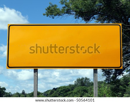 Big blank highway sign with blue sky and summer greens. - stock photo
