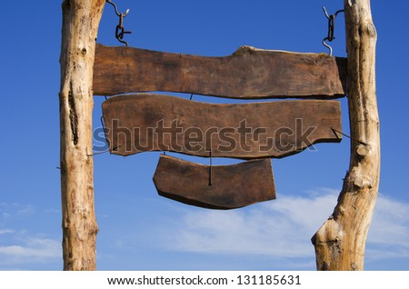 Big blank wooden sign. Three wooden boards were hung on two tall wooden pillars. - stock photo