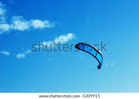 Big blue kite in the blue sky with some clouds - stock photo