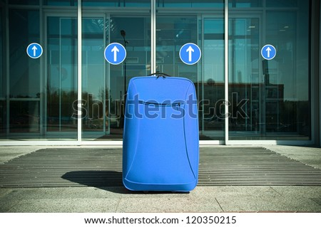 big blue suitcase waiting for traffic in front of the closed doors - stock photo
