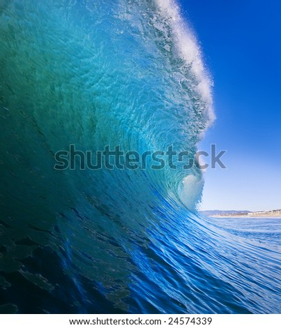 Big Blue Surfing Wave Breaks offshore, View of the Tube and Beach - stock photo