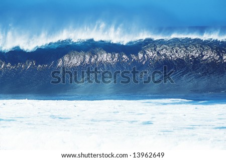 Big blue wave breaking and trowing off spray.  Horizontally framed shot. - stock photo