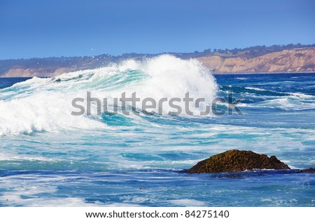 Big Blue Wave Breaks On La Jolla California's Pacific Coast, Torry Pines Cliffs with Sun and Clear Sky