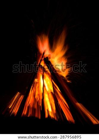 Big bonfire against dark night sky. Fire flames on black background. Zoom effect - stock photo