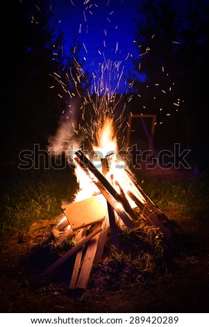 Big bonfire and sparks in the night. Orange fire is reaching for the sky. Forrest and trees in the background - stock photo