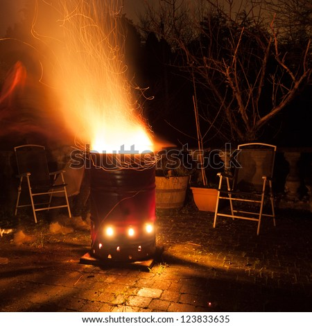 Big bonfire in a barrel at night with a rain of flying sparks - stock photo