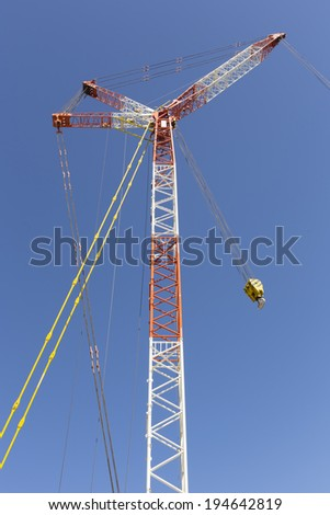 Big boom of crawler crane (red and white color) with blue sky background. - stock photo