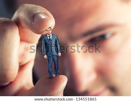 Big boss looking at small businessman in hand - stock photo
