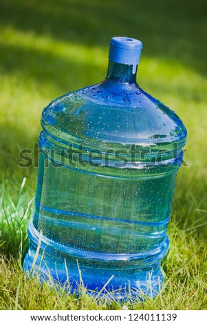 big bottle of water on green grass background - stock photo