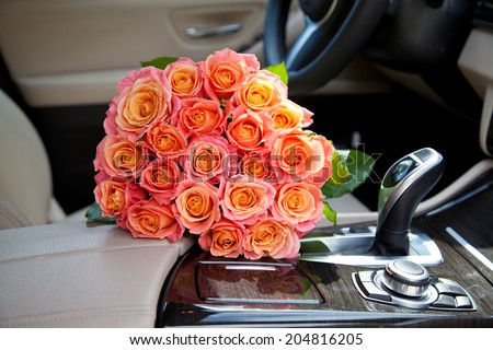 Big bouquet of colorful flower from beautiful fresh pink roses in luxury car. Valentines day romantic  - stock photo