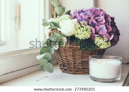 Big bouquet of fresh flowers, purple hydrangeas and white roses in a wicker basket on a windowsill, home decor, vintage style - stock photo