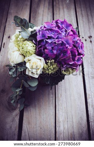 Big bouquet of fresh flowers, purple hydrangeas and white roses in a wicker basket on an old wooden board, vintage style