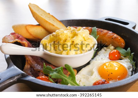 Big Breakfast or Brunch Set : Macaroni cheese, sausages, bacons, eggs, Garlic Breads served in sauce pan, selective focus - stock photo
